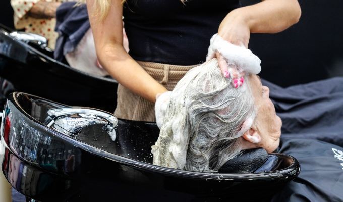 Salon client getting hair washed in basin