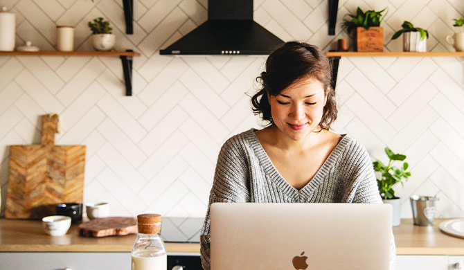 Woman in kitchen booking salon appointment on laptop