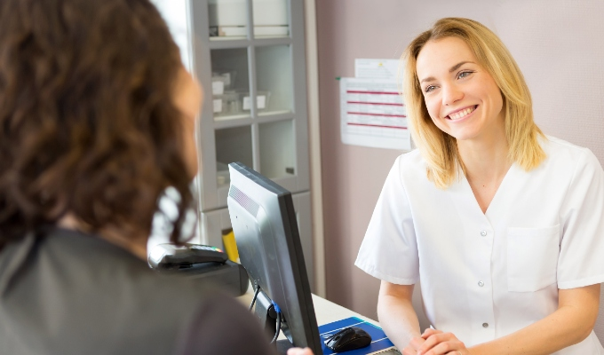 Clinic worker booking a client at reception